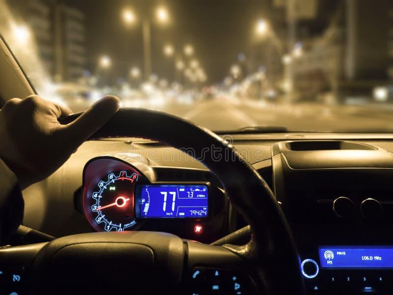 Samochodowy używa na nocy drodze mężczyzny mienia kierownica w samochodzie zdjęcia stock