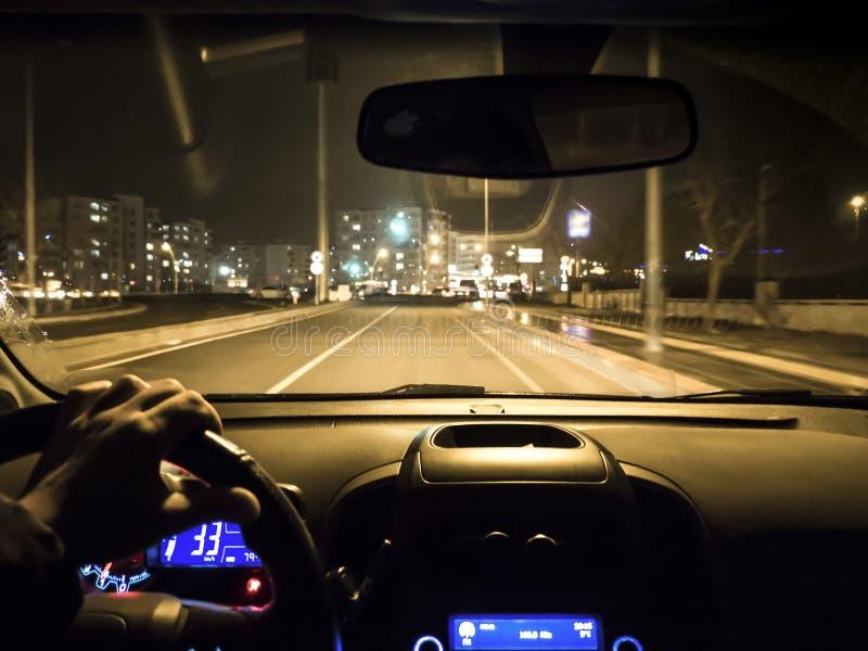 Samochodowy używa na nocy drodze mężczyzny mienia kierownica w samochodzie fotografia royalty free