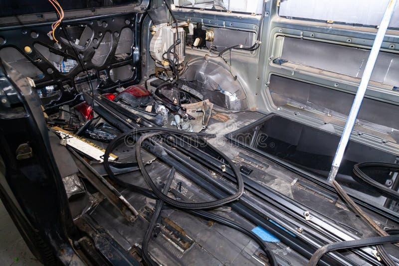 Samochodowy wnętrze z tyłu samochodu dostawczego z demontującą futrówką, siedzenia usuwał, dodatkowe części kłama na podłogowym s zdjęcie stock