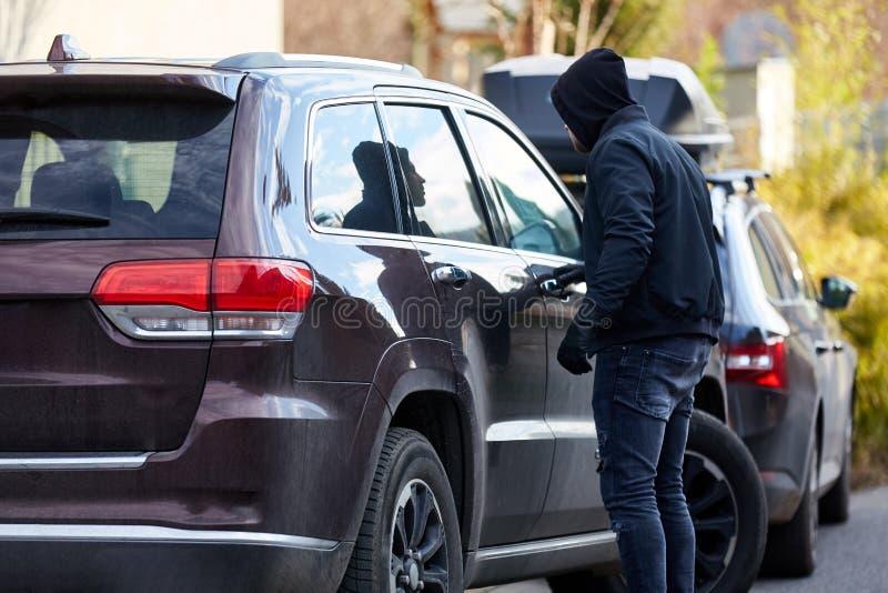 Samochodowy złodziej na samochodzie przy samochodową kradzieżą zdjęcia stock