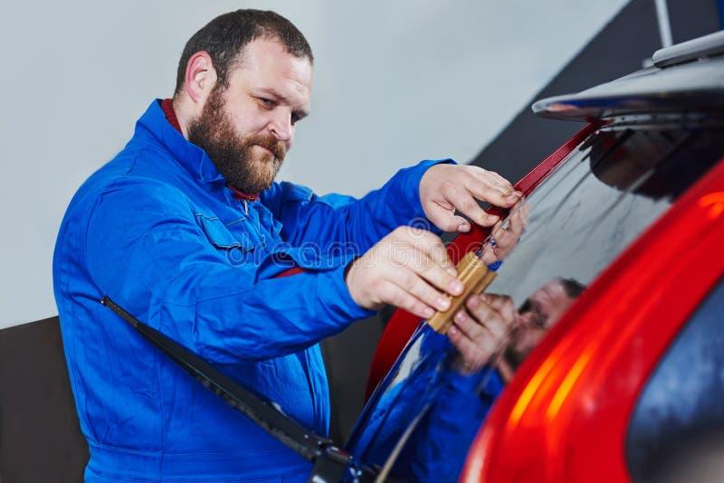 Samochodowy zabarwiać Samochodu mechanika technik stosuje folię zdjęcia stock