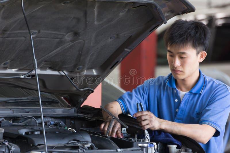 Samochodu mechanik egzamininuje samochodowego zawieszenie podnoszący samochód obraz royalty free