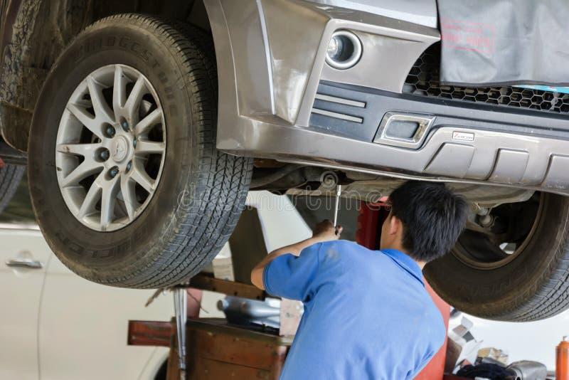 Samochodu mechanik egzamininuje samochodowego zawieszenie podnoszący samochód fotografia stock