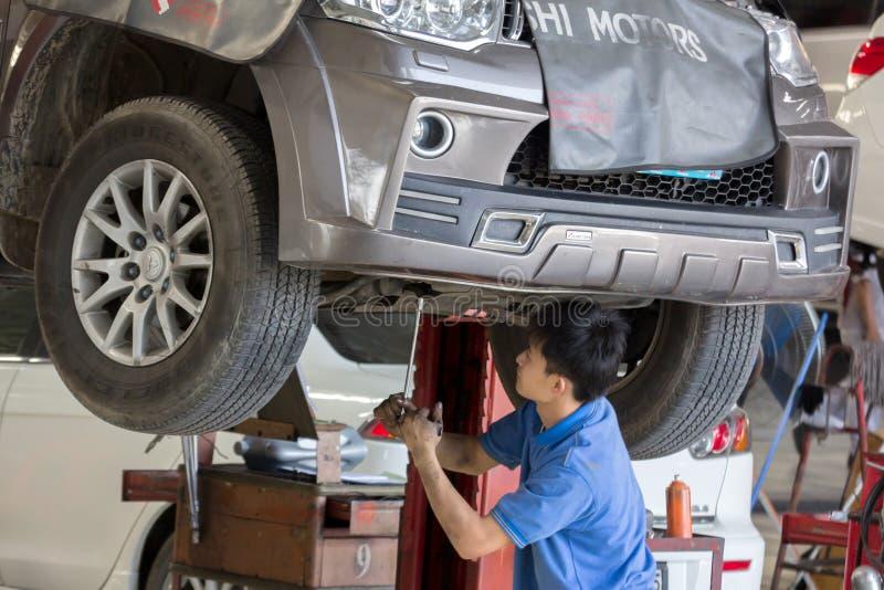 Samochodu mechanik egzamininuje samochodowego zawieszenie podnoszący samochód zdjęcia royalty free