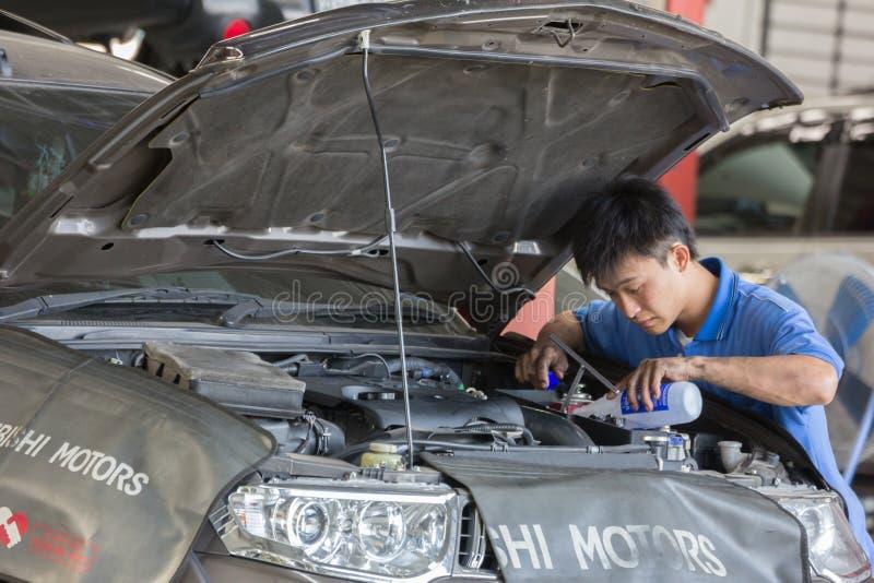 Samochodu mechanik egzamininuje samochodowego zawieszenie podnoszący samochód zdjęcie stock