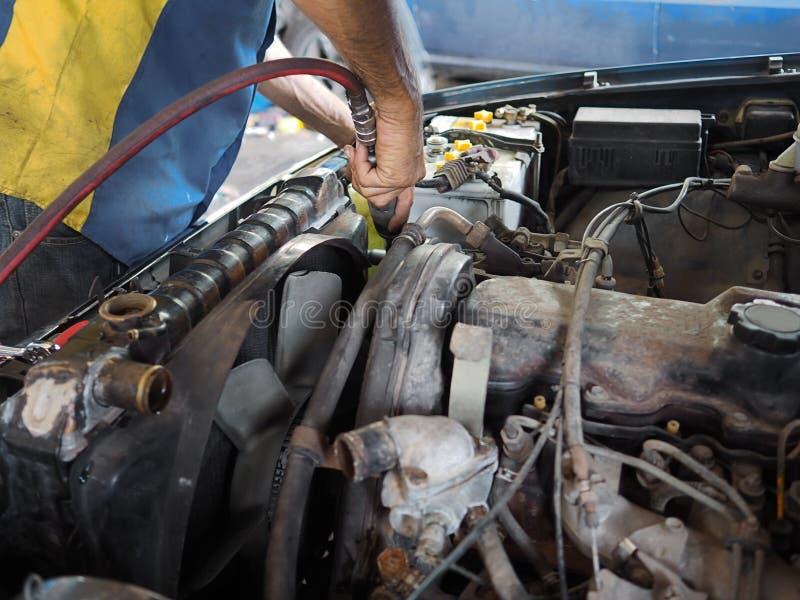 Samochodu mechanik sprawdza samochodowego silnika w garażu z narzędziami w rękach Auto remontowa usługa obrazy stock