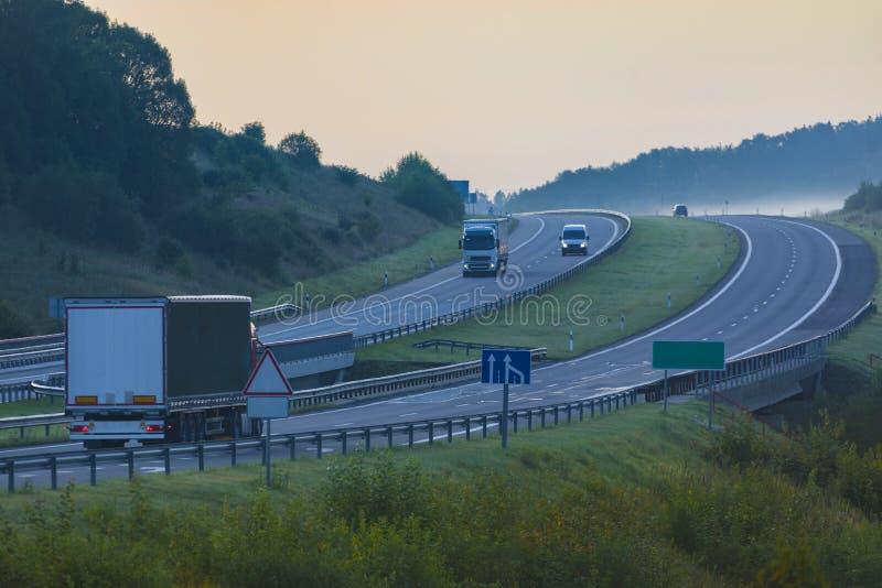 Samochody ciężarowe na autostradzie we wczesnym porannym lecie fotografia stock
