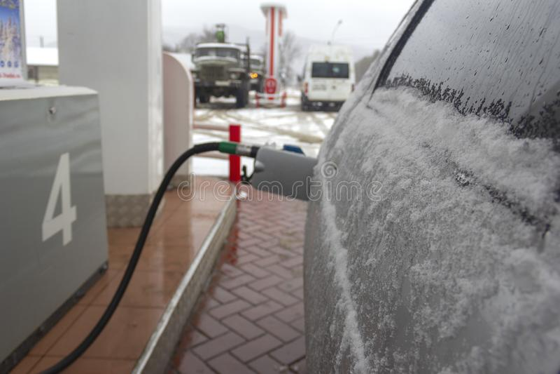 Samochody w śniegu przy benzynową stacją w zimie, pistolet w benzynowym zbiorniku tło wizerunek zdjęcia royalty free