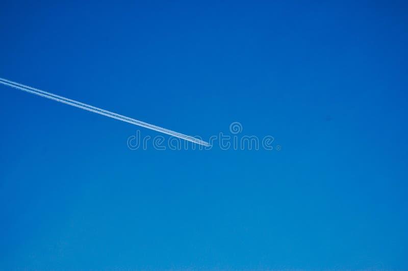 Samolot lata przez niebo opuszcza białych ślada zdjęcie royalty free