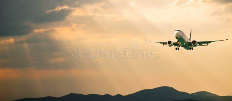 Samolot pasażerski Pejzaż z przodu białego samolotu leci na pomarańczowym niebie z chmurami nad górami, morze w kolorze zdjęcie stock