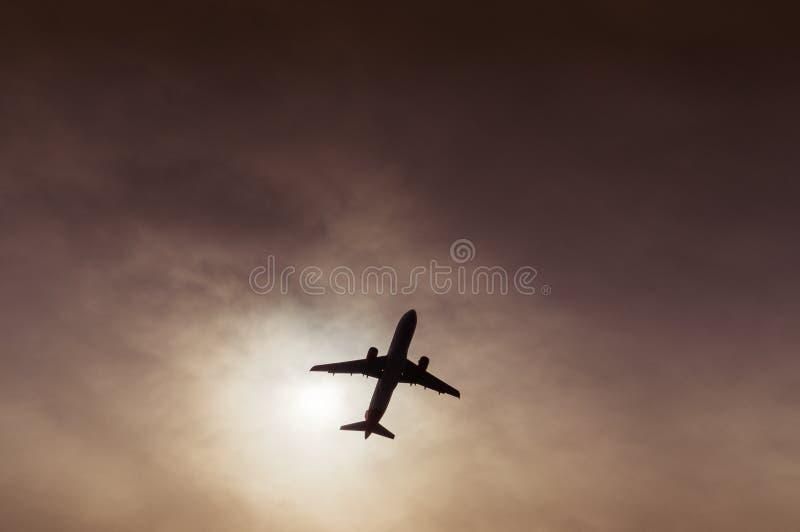 Samolot sylwetka widoczna pod rozcięciem w chmurach obraz royalty free