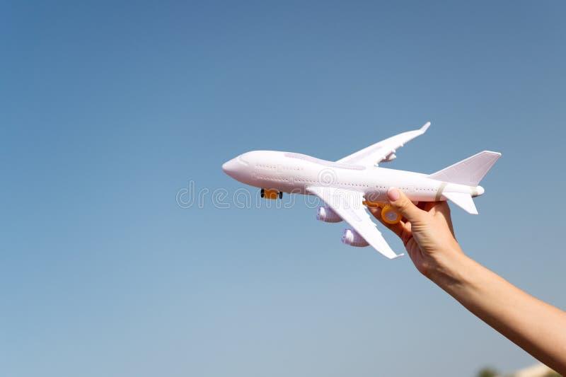 Samolot w żeńskiej ręka jasnego niebieskiego nieba tła kopii przestrzeni Podróż i Wakacje Książkowi bilety teraz Zabawkarska biał zdjęcia stock