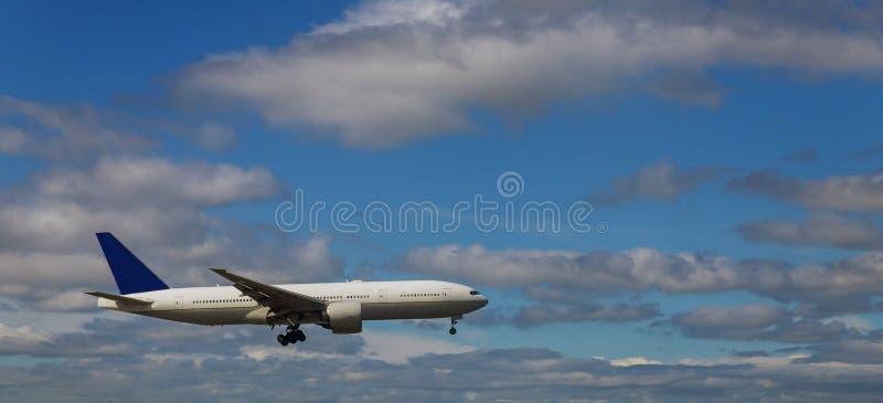 Samolot w niebie iść lądowanie przeciw białe puszyste chmury zdjęcie royalty free