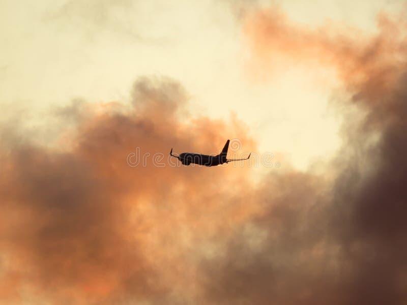 Samolot wylatuje przez dramatyczne chmury oświetlone słońcem tego wieczoru obrazy royalty free