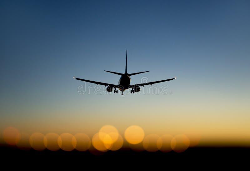 Samolot zbliża się lotnisko przy zmierzchem fotografia stock