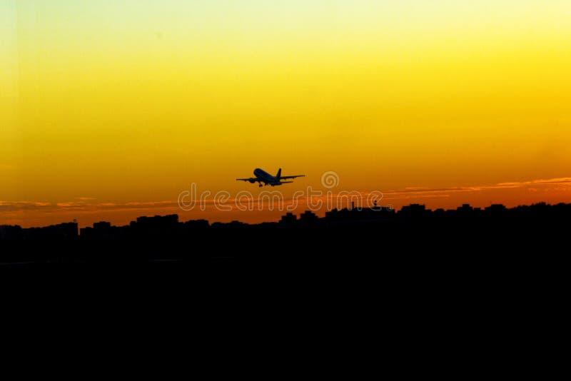 Samolot zdejmował przy zmierzchu koloru żółtego słońcem obrazy royalty free