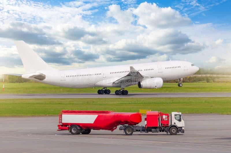 Samolot zdejmuje od pasa startowego przy lotniskiem w przedpolu, ciężarówka z lotnictwo paliwowym zbiornikiem zdjęcia royalty free