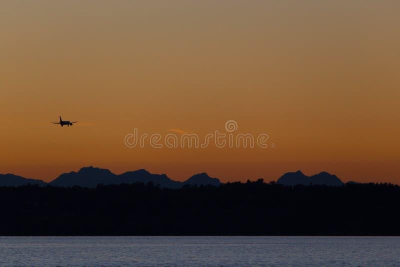 Samolotowy latanie nad wzgórzami i morzem przy zmierzchem obrazy royalty free