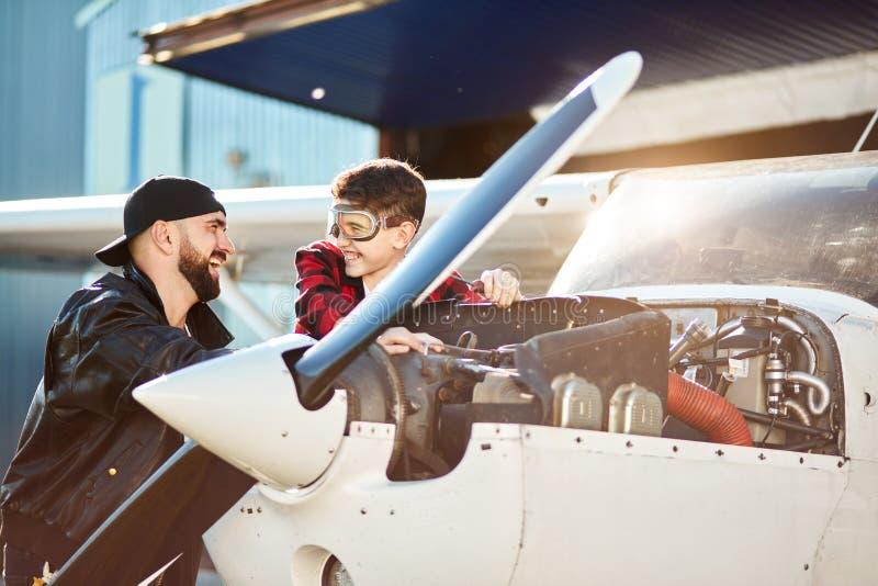 Samolotu inżynier i jego brat stoi blisko samolotu, mówjący śmieszne opowieści i śmiać się obrazy royalty free