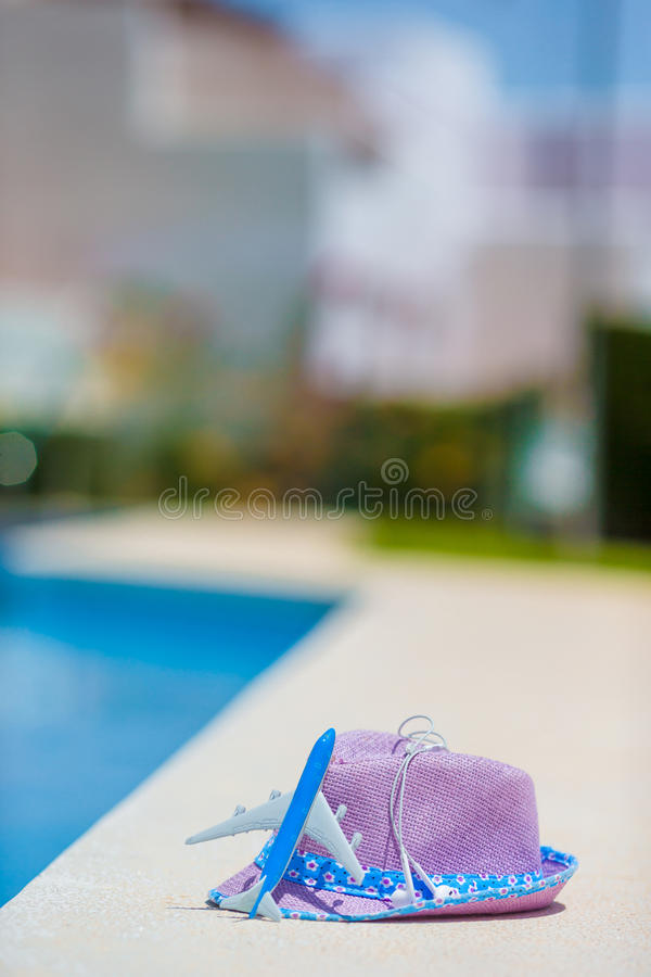 Samolotu wzorcowy i słomiany purpurowy kapeluszowy pobliski pływacki basen przy latem zdjęcie stock