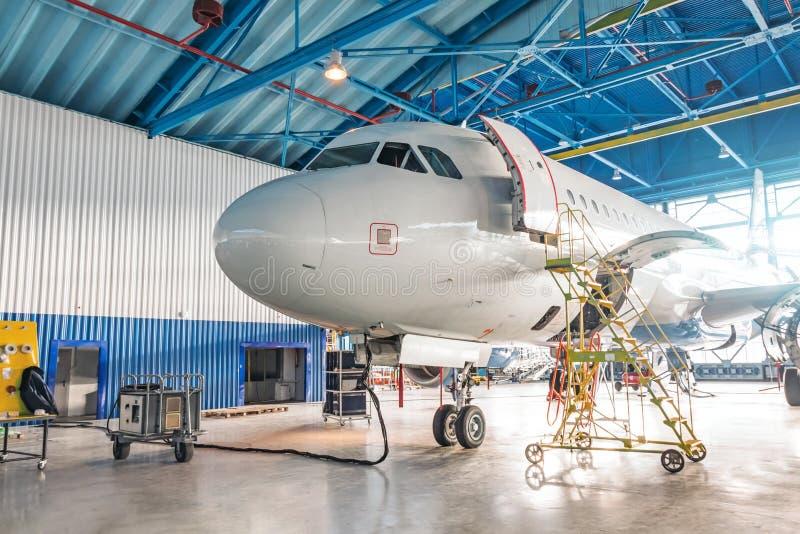 Samoloty będące w trakcie naprawy w hangarze obsługi technicznej Widok na nos i kokpit, otwarte drzwi przednie ze schodami techni zdjęcie stock