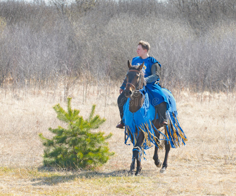 SAMOLVA, PSKOVSKAYA OBLAST, RÚSSIA - 22 DE ABRIL: cavaleiro de horseback unindentified em um cavalo da reconstrução histórica do B foto de stock