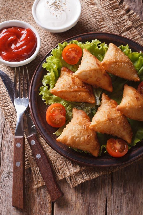 Samosa indiano su un piatto con il primo piano della salsa, vista superiore verticale immagine stock