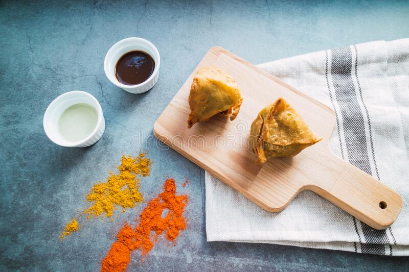 Samosas on a table with spicy and sesame sauce. Indian food. Free meat snack.  Close up view royalty free stock photos