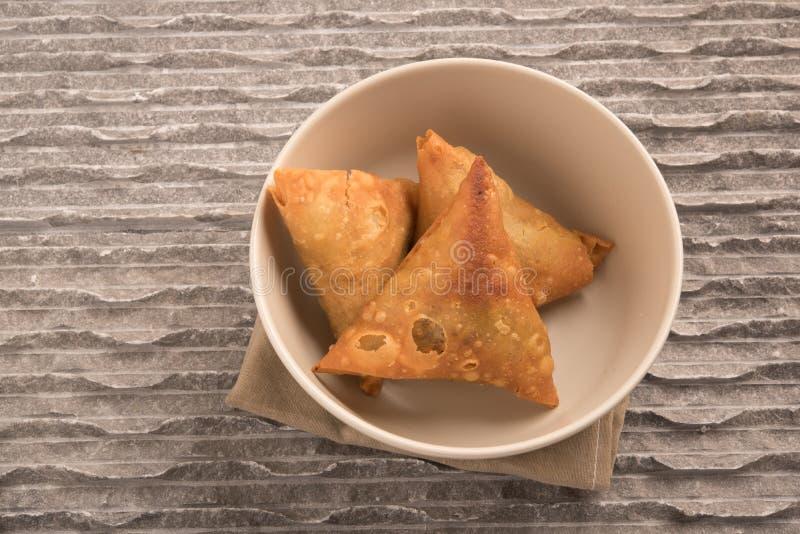 Samosas un mélange épicé des légumes ou de la viande enveloppés dans un colis triangulaire cuit à la friteuse de pâtisserie dans  photographie stock libre de droits