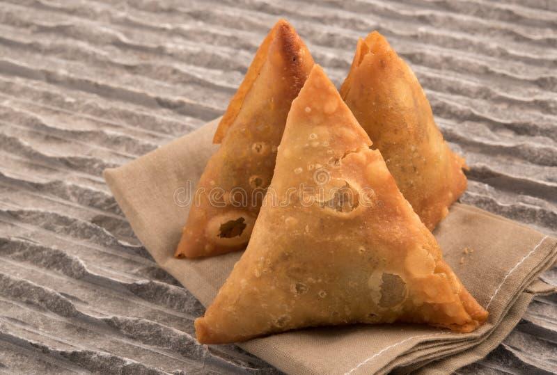 Samosas un mélange épicé des légumes ou de la viande enveloppés dans un colis triangulaire cuit à la friteuse de pâtisserie image libre de droits