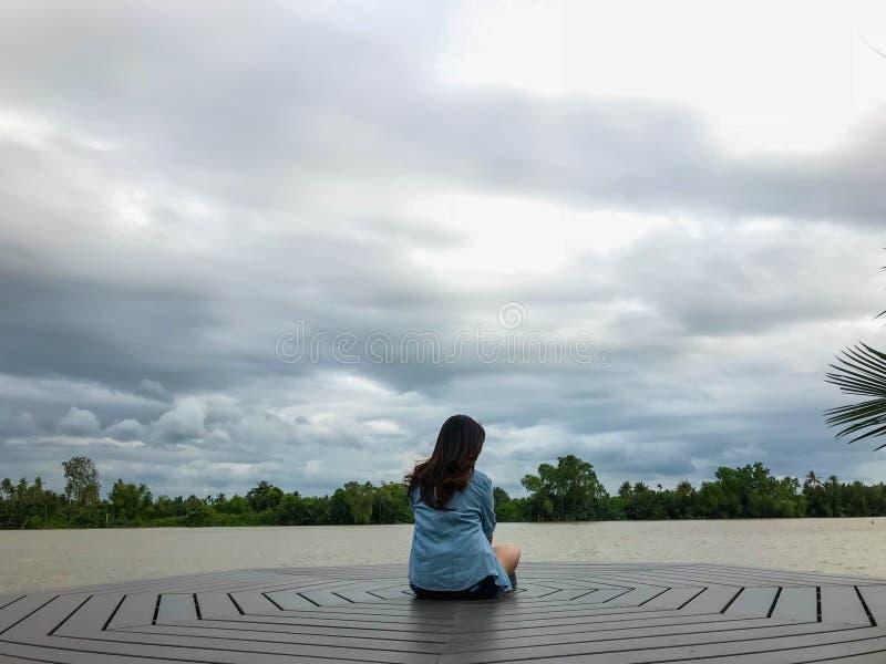 Samotna dama siedzi na nabrzeżu zdjęcie royalty free