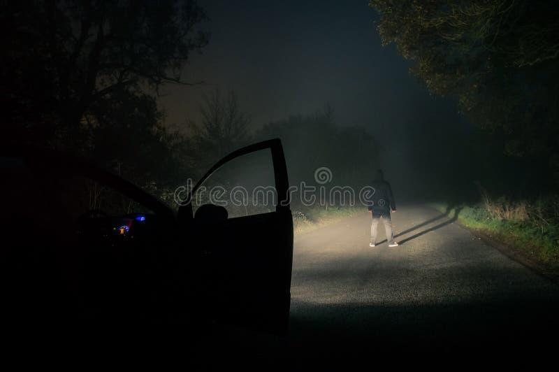 Samotna kapturzasta postaci pozycja na pustej mglistej strasznej drodze przy nocą Podkreślający z samochodowymi reflektorami zdjęcia stock