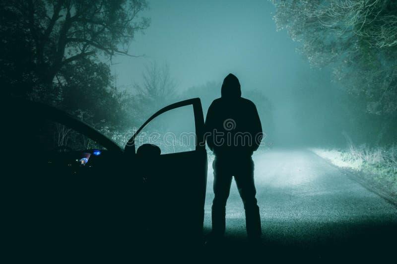 Samotna, kapturzasta postaci pozycja obok samochodu patrzeje pustego, zdjęcia royalty free