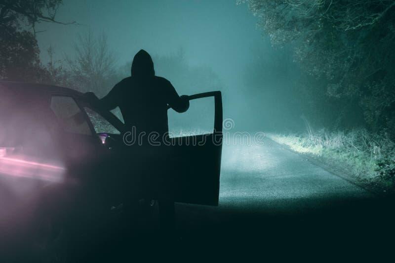Samotna, kapturzasta postaci pozycja obok samochodu patrzeje pustego, zdjęcia stock