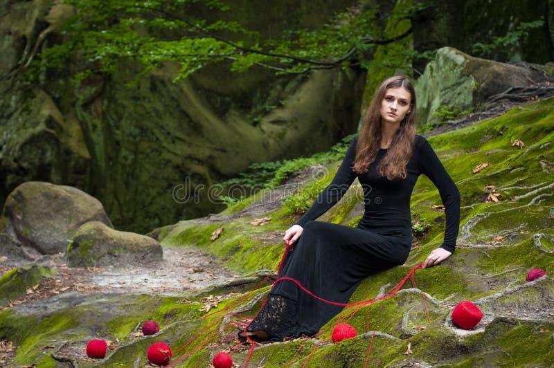 Samotna piękna dziewczyna siedzi na zielonym mech w czarodziejskim lesie fotografia stock