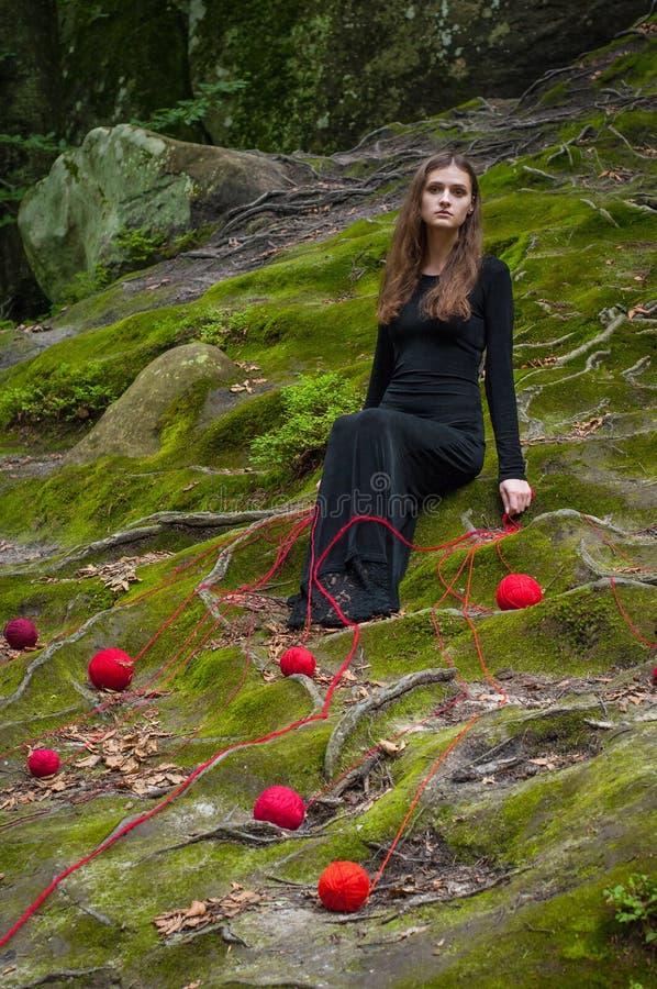 Samotna piękna dziewczyna siedzi na zielonym mech w czarodziejskim lesie zdjęcia royalty free