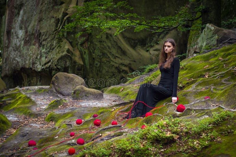 Samotna piękna dziewczyna siedzi na zielonym mech w czarodziejskim lesie obraz stock