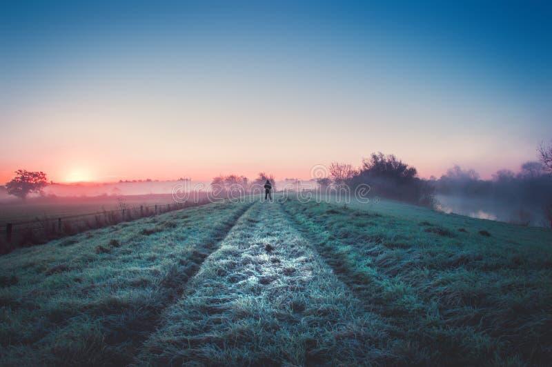 Samotna postać sylwetkowa mglistą rzeką przy wschodem słońca na ścieżce obrazy stock