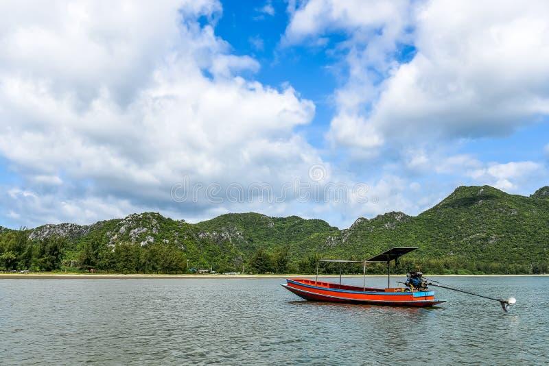 Samotne łodzie rybackie unoszą się na morzu z niebieskim niebem i chmurnieją tło obraz stock