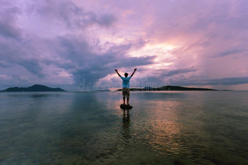 Samotnego mężczyzna turystyczna pozycja na kamieniu w tropikalnym morzu i enjo obraz royalty free
