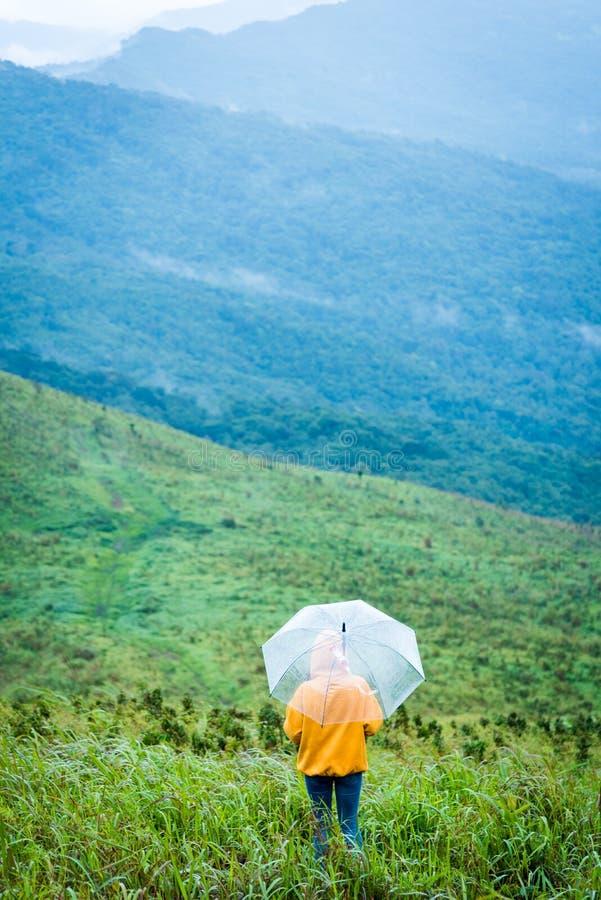 Samotny żeński wycieczkowicza mienia parasol i relaksować z dużym mounta obrazy stock