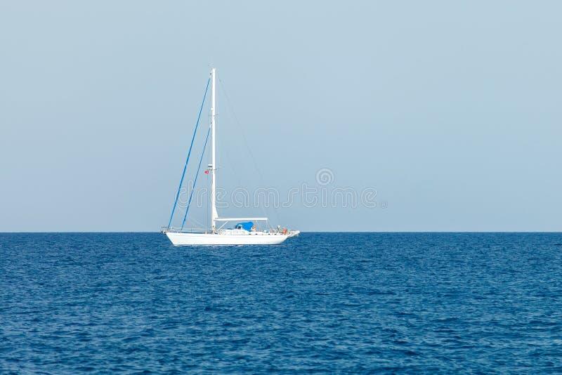 Samotny biały jacht z opuszczonymi żagli stojakami w wodach morze śródziemnomorskie zdjęcie stock