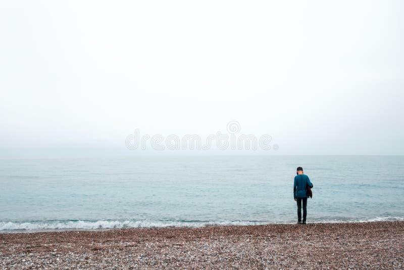 Samotny chłopiec pobyt blisko morza obraz stock