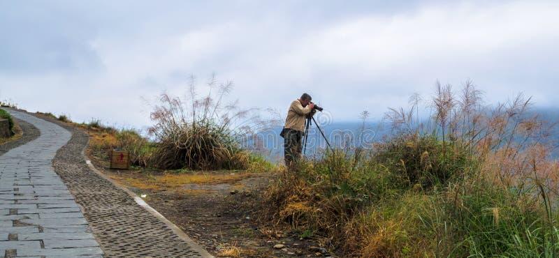 Samotny fotograf robi fotografiom w dżdżystej pogodzie przy Longsheng tarasował ryżowych pola, Guilin, Guangxi, Chiny obraz royalty free