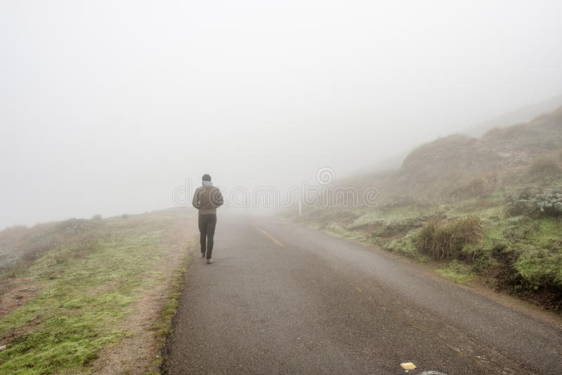 Samotny mężczyzna odprowadzenie przez białej mgły obraz stock