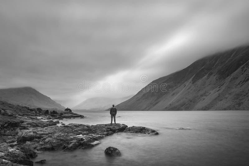 Samotny mężczyzna w krajobrazowym wizerunku Wast woda w UK Jeziornym okręgu podczas markotnego wiosna wieczór w czarny i biały zdjęcia royalty free