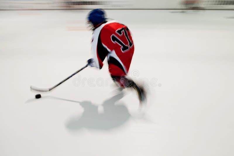 Samotny młody gracz w hokeja w czerwieni sukni z liczbą 17 w ruchu, rozmyty ruch na lodowym stadium obraz stock