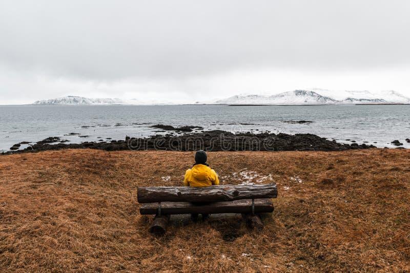 Samotny nieznany podróżnik w żółtej kurtce deszczowej relaksuje się w pięknym widoku morza i góry z drewnianą ławką w Reykjavi obrazy royalty free