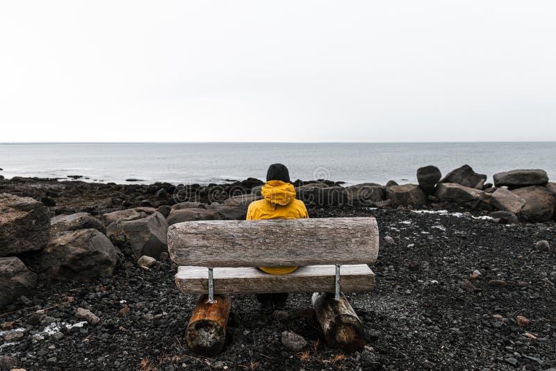 Samotny, nieznany podróżnik w żółtej kurtce deszczowej relaksuje się w pięknym widoku morza z drewnianą ławką w Islandii zdjęcie stock
