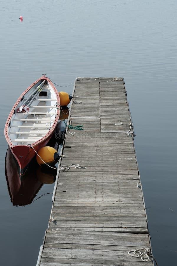 Samotny stażowy naczynie siedzi przy drewnianym dokiem na Maine wybrzeżu zdjęcie royalty free